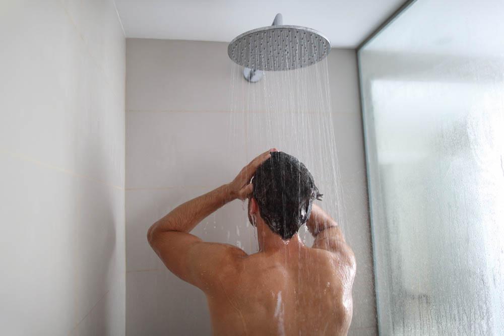 Chico en la ducha, usando agua caliente con gas natural