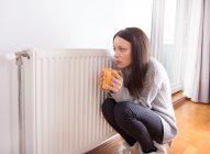 Chica con una taza en las manos pasando frío al lado de un radiador porque posiblemente no funcione correctamente