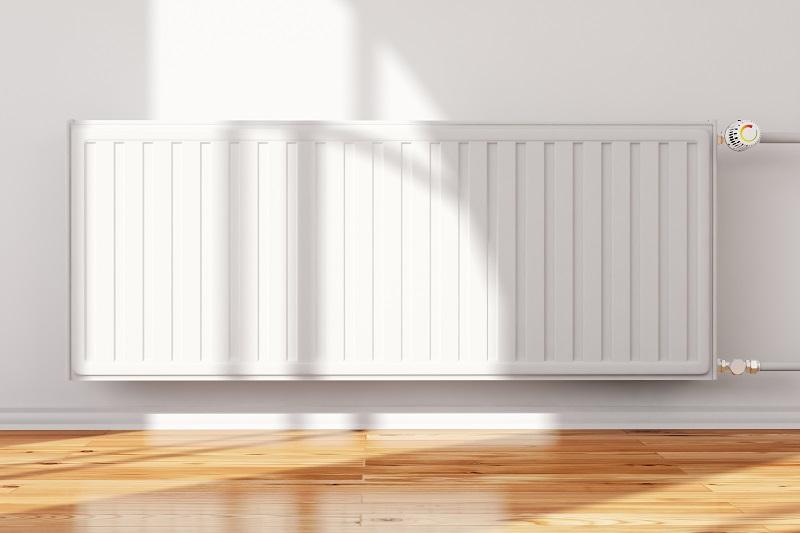 Pared blanca con un radiador de gas natural y suelo de parquet