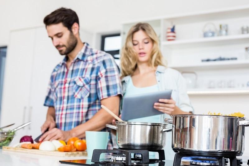 Pareja en la cocina, cocinando espaguetis con gas natural