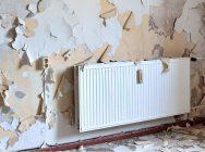 pared con pintura levantada con un radiador de gas natural