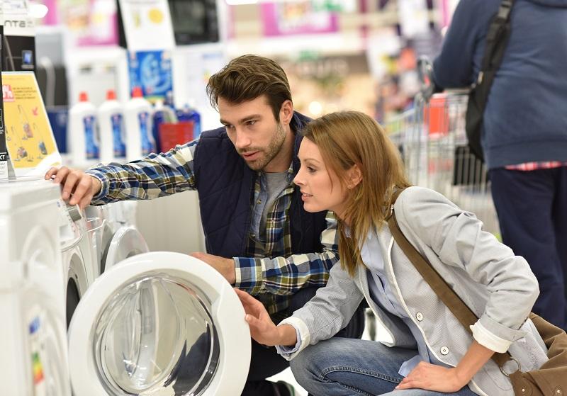 Pareja escogiendo lavadora a gas natural en una tienda de electrodomésticos