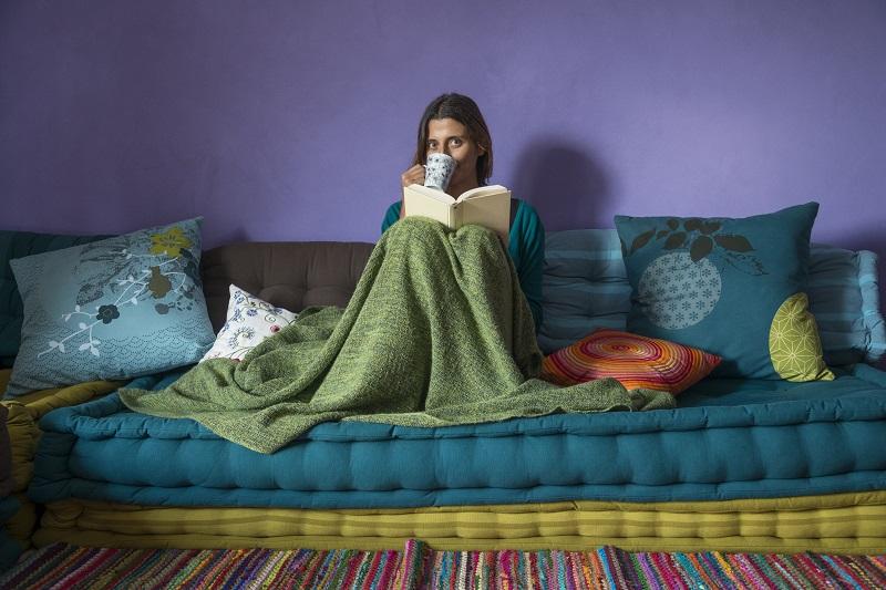 Chica en la cama tapada con una manta y tomando café mientras lee un libro asustada