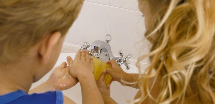 Nens que es renten les mans amb aigua calenta sanitària
