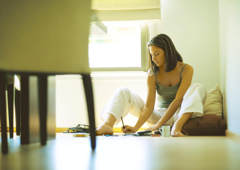 Plan renove calderas. Chica sentada en el suelo haciendo cálculos de coste