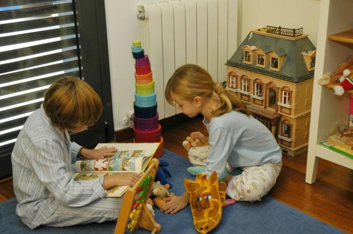 Niños jugando delante de radiador de gas natural