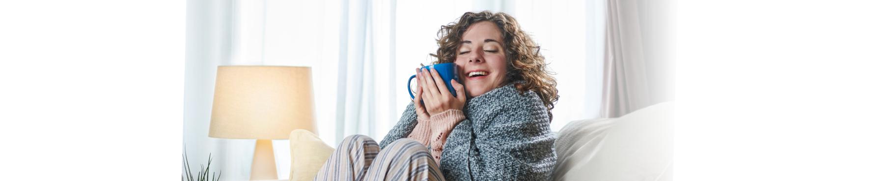 Contratar gas natural - Chica con taza de café en el sofá